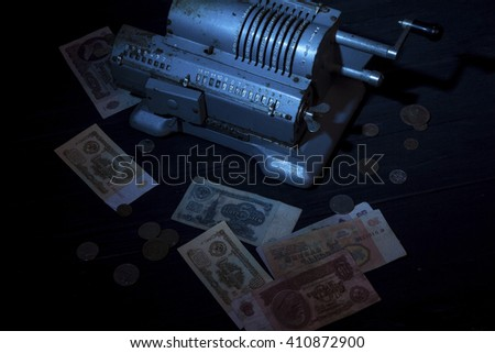 The old adding machine on the dark blue wooden table with soviet money around.