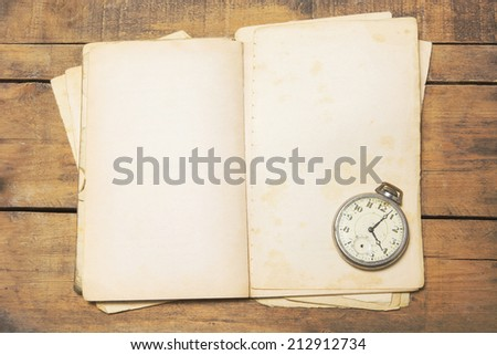 The old and broken pocket watch on the old book - stock photo