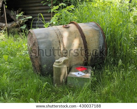 The old barrel for gasoline. Barrel is metal and rusty. Ecological dangerous. - stock photo