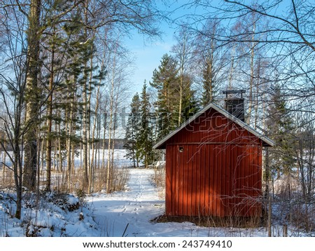 The old bathhouse in the woods by the lake, clear winter day. - stock photo