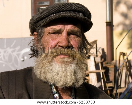 The old bearded man on a urban background - stock photo