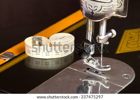 The Old black sewing machine with soft meter on it