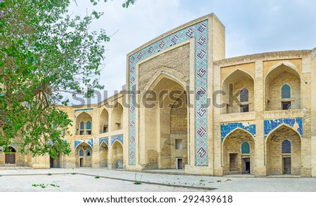 The old brick courtyard of Modari Khan Madrassah with the remains of the tiled traceries on the walls, Bukhara, Uzbekistan.