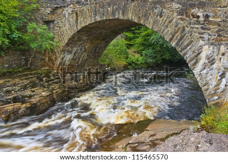 The old Bridge of Dochart, where the River Dochart flows through the village of Killin in the highlands of Scotland, near the area of waterfalls and white water rapids known as the Falls of Dochart. - stock photo