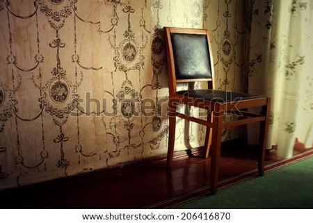 the old chair rubbed from time costs in the room - stock photo