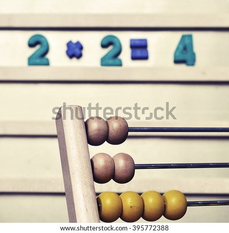 The old children's toy magnets, and abacus. Two plus two equals four. Vintage toning.  - stock photo