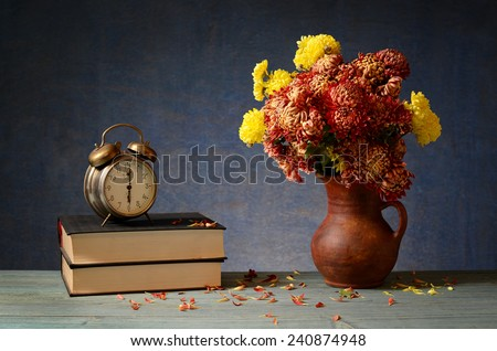 The old clock, books and flowers in a vase - stock photo