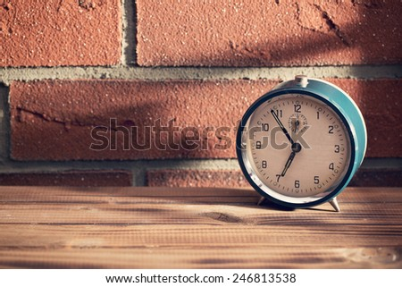 The old clock in front of a brick wall - stock photo