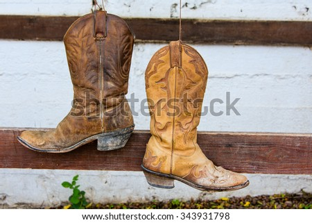 The old cowboy boots hanging on the bar in front of the stables - stock photo