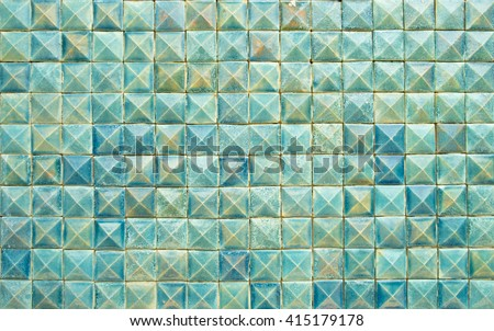 the old dark blue and green wall tiles, chipped tiles, dirty tiles, the alkali blue and green tiles wall, rust on wall tiles, the blue and wall tiles of the building background texture - stock photo