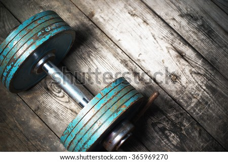 The old dumbbell on the wooden floor. flat lay - stock photo