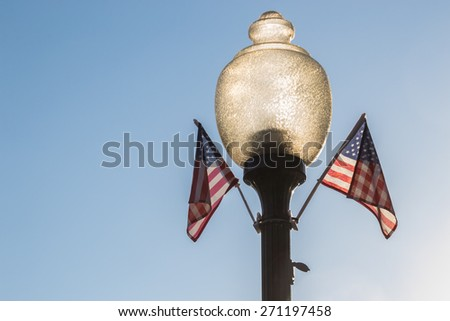 The old fashioned lamp with small American flags. - stock photo