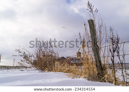 The old fence line with rural country farmhouse in the snowy background. - stock photo