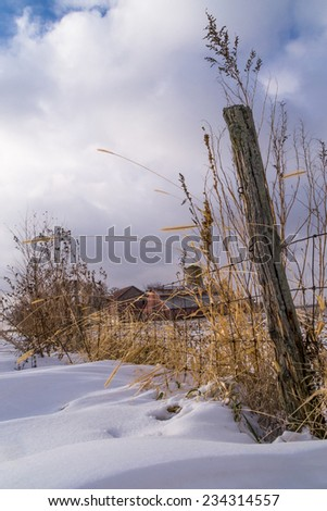 The old fence line with rural country farmhouse in the snowy background.