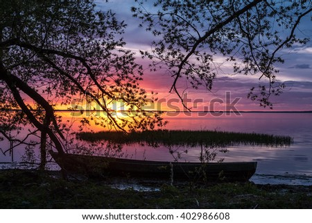 the old fishing boat on the overgrown coast in evening paints of a summer decline in Pereslavl
