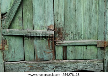 The old green shutters of window with metallic hooks. Abstract - stock photo