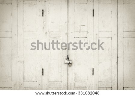 The old grunge folding door closed in B&W. - stock photo