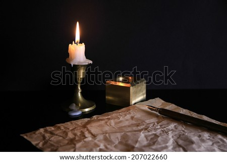 The old handle feather and a sheet of paper with a candle