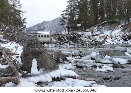 The old hydroelectric power station on the river  after a flood in mountain Altai in Russia - stock photo