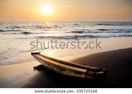 The old Indian fishing boat on the beach at sunset in Kerala.