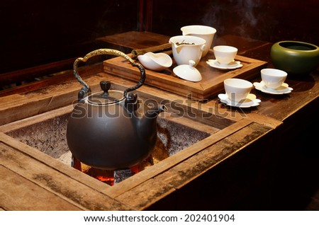 The old kettle put on a fireplace  - stock photo