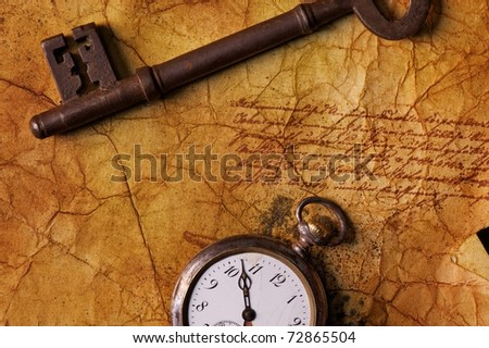 The old key with a clock on the textured paper - stock photo