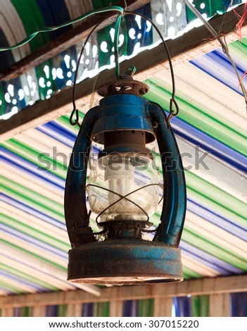 The old lamp hangs on beam colorful blur background. - stock photo