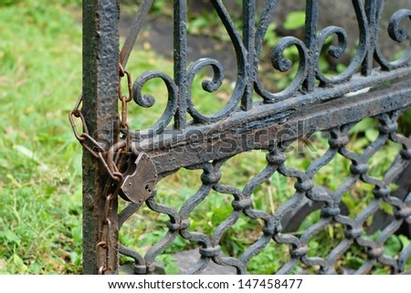 The old lock through a chain weighs on gate of an old fencing from iron