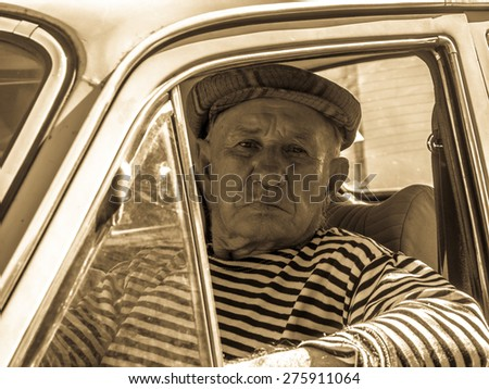 the old man behind the wheel of an old car. Retro stylized photo. - stock photo