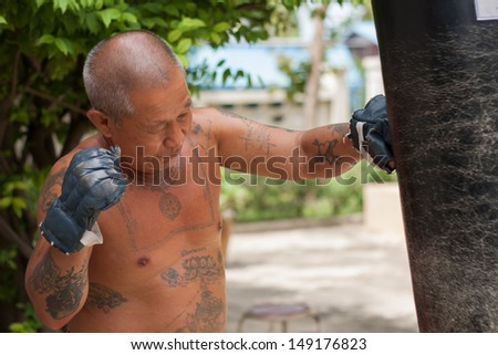 The old man boxer practicing boxing, his body full of tattoo
