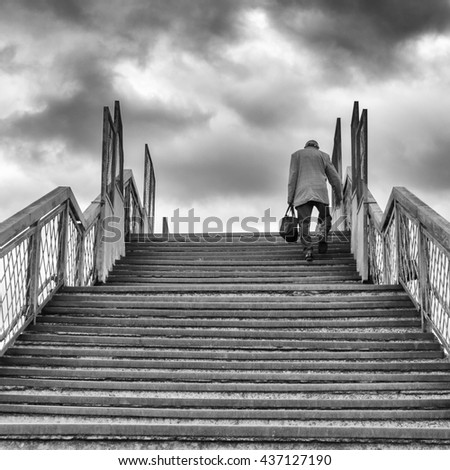 The old man climbs the stairs - stock photo