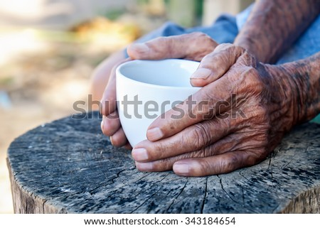The old man hand holding a coffee cup on the wood - stock photo