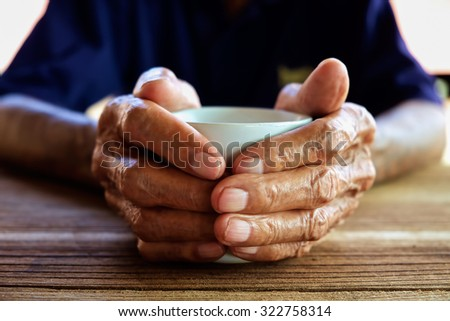 The old man hand holding a coffee cup on the wood table  - stock photo