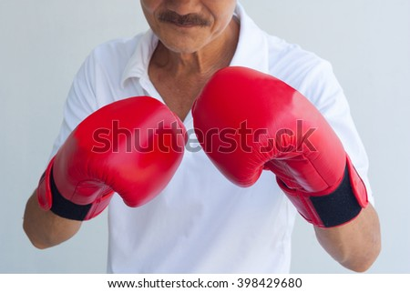 The old man in boxing gloves.Boxer fighter over black background.