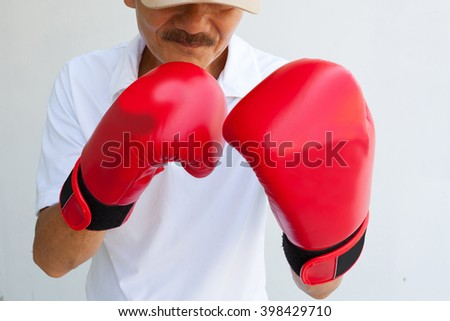 The old man in boxing gloves. Boxer fighter over black background.