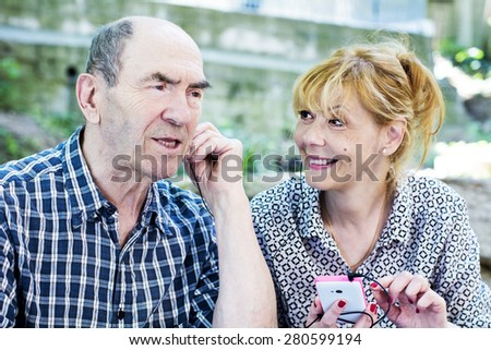 The old man listens to music from a mobile phone  - stock photo
