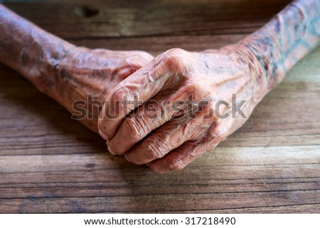 The old man sat holding hands on a wooden table. - stock photo
