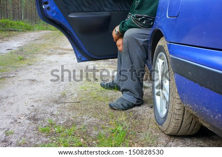 The old man sitting in a car on a forest road - stock photo