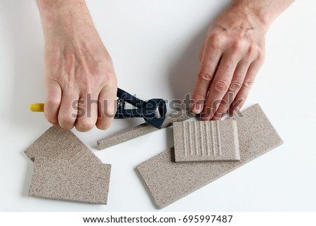 The old master ticks and cut the pieces of ceramic tiles on his work white table.