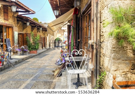The old medieval pedestrian souk in Byblos, Lebanon during the day. A view of the little shops and streets paved with little stones. - stock photo