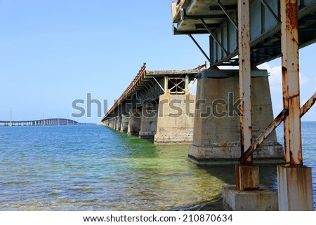 The old Overseas Railroad in the Florida Keys, now missing sections, was later converted to a roadway, then replaced with a  more modern highway. - stock photo