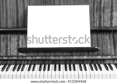 The old piano and sheet of white paper. Close-up view. White background for text and advertising. - stock photo