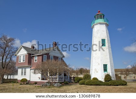 The Old Point Comfort lighthouse, a part of the new Fort Monroe National Monument, with the keepers quarters in winter against a bright blue sky with white clouds - stock photo
