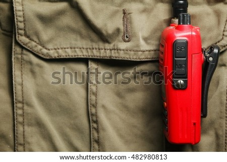 The old portable radio put on pant pocket represent the adventure wear and communication equipment concept related background.