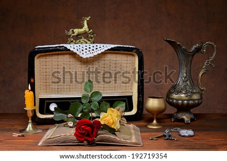 The old radio, a metal jug and roses on the table