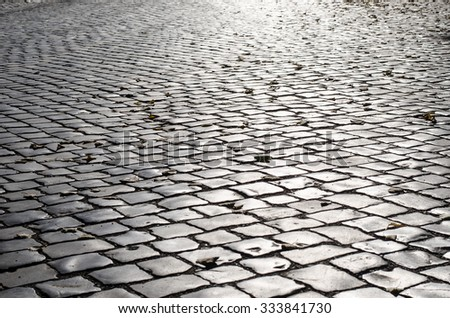 The old road is paved with stone setts - stock photo