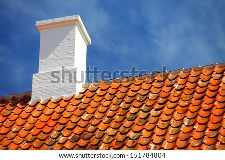 The old roofing tiles red clay house roof with chimney sky background - stock photo