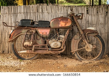 the old, rusty motorcycle on a street - stock photo