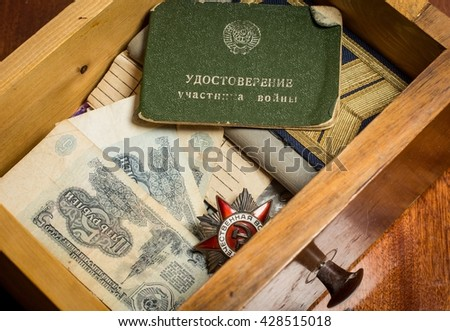 The old Soviet military awards and money in a wooden box - stock photo