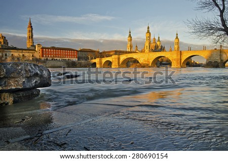 The old stone bridge across Ebro river in Zaragoza  in early morning lights of sunrise,  Basilicaâ??Cathedral of Our Lady of the Pillar is behind, the the water flow is at background